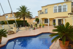 Beautiful villa for sale on canal at the entrance of the marina in Empuriabrava, Costa Brava, with 4 bedrooms, heated pool, outdoor kitchen and large mooring.