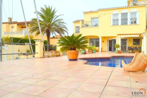 Beautiful villa for rent on canal at the entrance of the marina in Empuriabrava, Costa Brava, with 4 bedrooms, heated pool, outdoor kitchen and mooring.